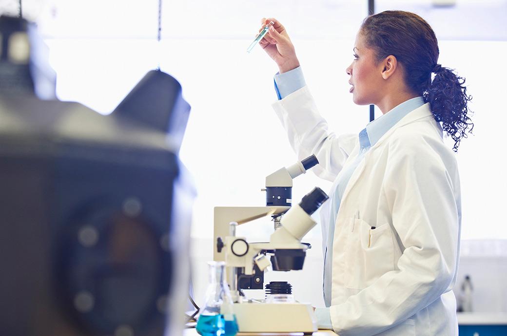 Une docteure dans un laboratoire regardant dans un microscope.