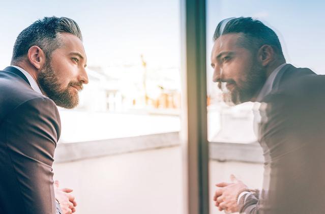 Image d'un homme mature regardant sa réflexion au travers d'une fenêtre.