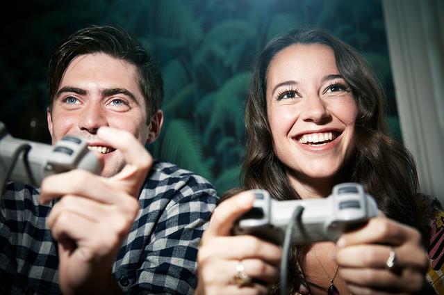 Deux adultes manettes à la main jouant aux jeux vidéo.