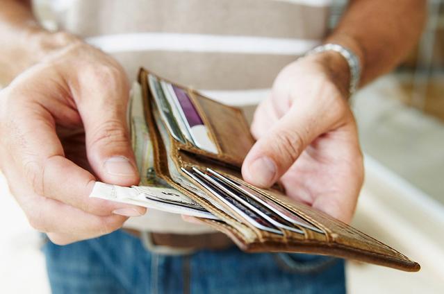 Gros plan sur quelqu'un sortant des billets de son portefeuille.
