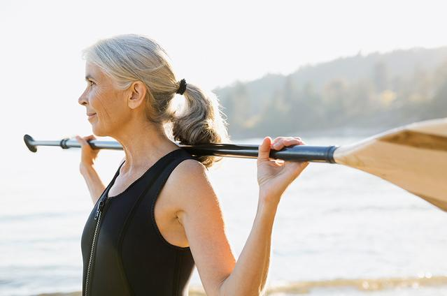 Image of a mature woman outside with a paddle
