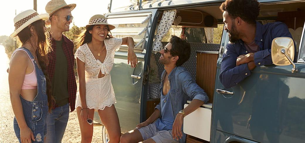 Un groupe d'amis discutant et rigolant près d'un van