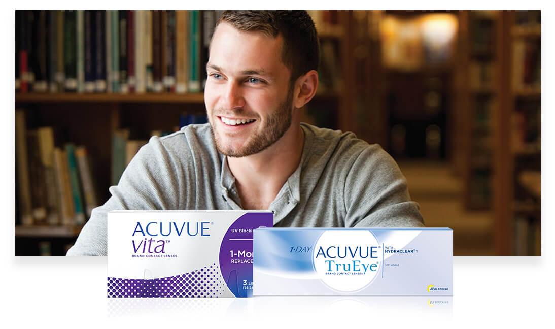 Un jeune homme à la bibliothèque, souriant et regardant face à lui