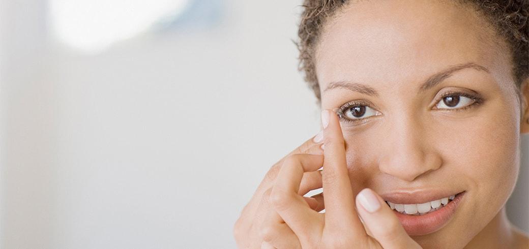 Une femme avec une lentille de contact sur son doigt sur le point de la poser sur son oeil
