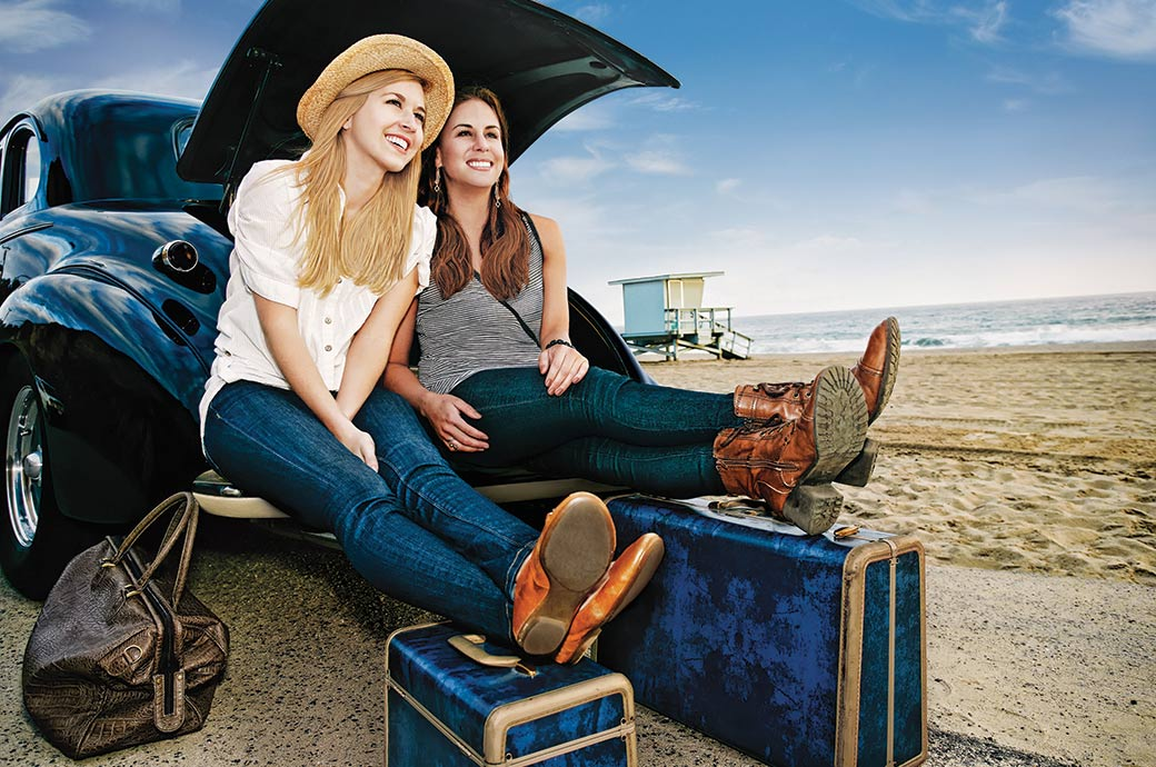 Two girls sitting in the boot of a car by the beach with their luggage ready to go on holiday.